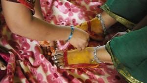 kvinne får føttene malt med gurkemeie og kumkum under sumaṅgalīpūjā. Disse er lykkebringende substanser som er viktige i hinduritualer.